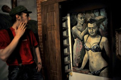 A file picture taken on August 21, 2013, shows a visitor looking at an artwork by Russian artist Konstantin Altunin representing Russia's President Vladimir Putin and Prime Minister Dmitry Medvedev in women's lingerie.  AFP PHOTO/OLGA MALTSEVA.